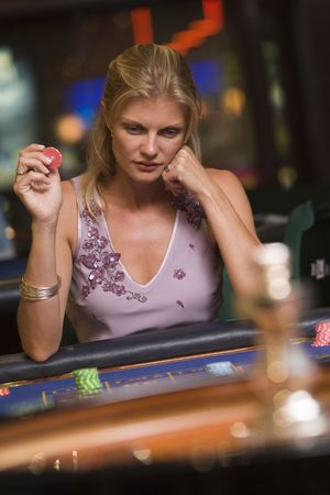 gambling parlors: Woman in casino playing roulette and holding chip (selective focus)