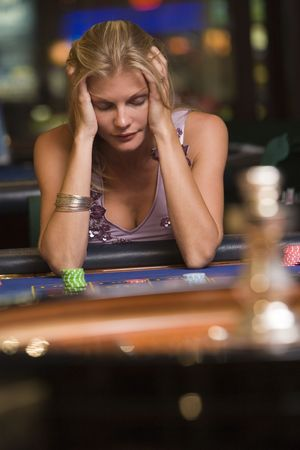 gambling parlour: Woman in casino playing roulette and losing (selective focus)