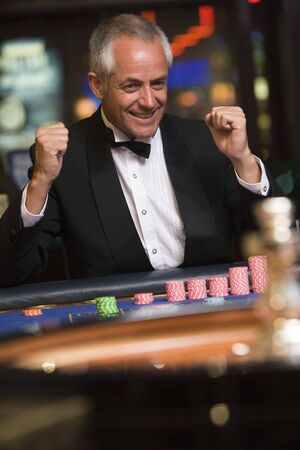parlours: Man in casino winning roulette smiling (selective focus)