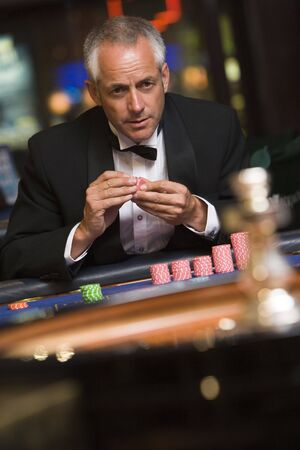 parlour games: Man in casino playing roulette holding chips (selective focus)
