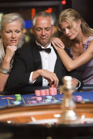 gambling parlors: Three people in casino playing roulette smiling (selective focus) Stock Photo