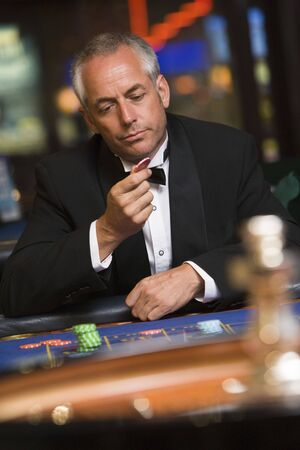 caucasoid race: Man in casino playing roulette and looking at chip (selective focus)
