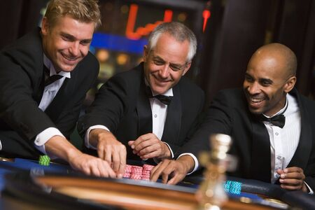 gambling parlors: Three men in casino playing roulette smiling (selective focus)
