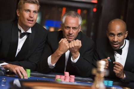 gambling parlors: Three men in casino playing roulette (selective focus)