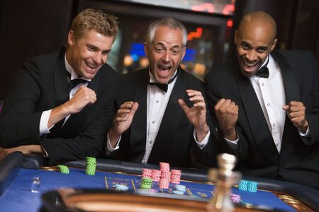 Three men in casino playing roulette smiling (selective focus)