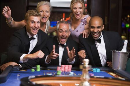 caucasoid race: Five people in casino playing roulette smiling (selective focus)