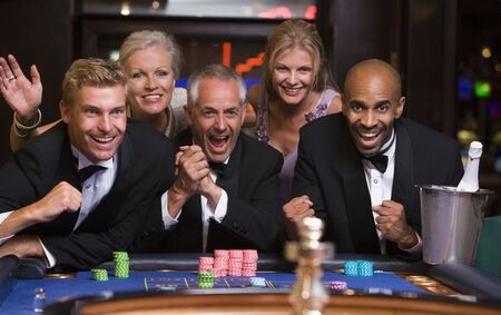 Five people in casino playing roulette smiling (selective focus)