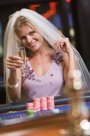 caucasoid race: Woman in bridal veil in casino playing roulette and smiling (selective focus)