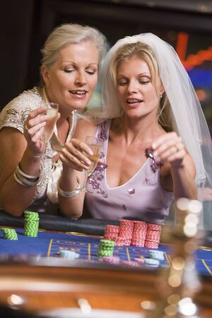 gambling parlour: Woman in bridal veil with another woman in casino playing roulette and smiling (selective focus)
