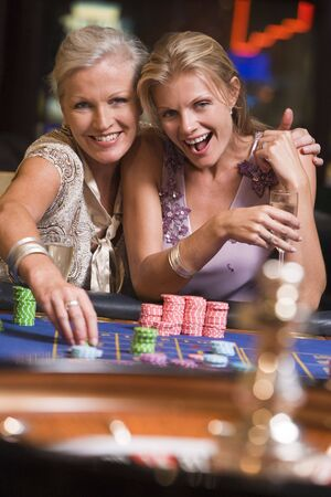 roulette wheels: Two women in casino playing roulette and smiling (selective focus)