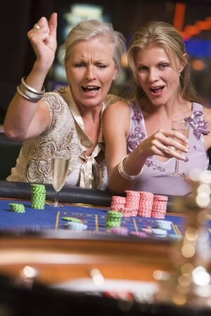 gambling parlors: Two women in casino playing roulette and smiling (selective focus)