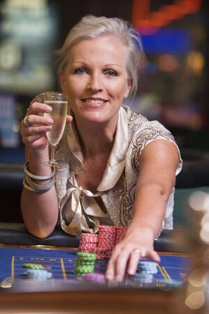 gambling parlour: Woman in casino playing roulette and smiling (selective focus)