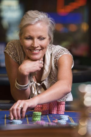 caucasoid race: Woman in casino playing roulette and smiling (selective focus)