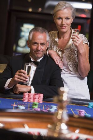 gambling parlors: Couple in casino playing roulette and smiling (selective focus) Stock Photo