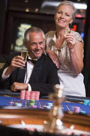 Couple in casino playing roulette and smiling (selective focus) Stock Photo - 3194462