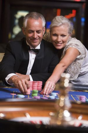 caucasoid race: Couple in casino playing roulette and smiling (selective focus) Stock Photo