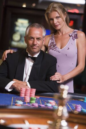 gambling parlour: Couple in casino playing roulette and smiling (selective focus) Stock Photo