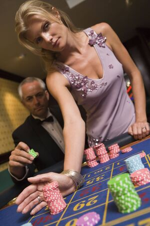 gambling parlors: Couple in casino playing roulette (selective focus)