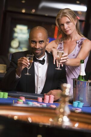 gamers: Couple in casino at roulette table holding champagne and smiling (selective focus)