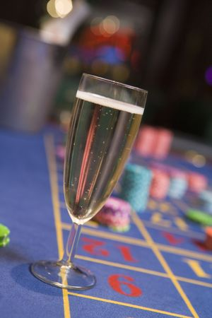 gambling parlors: Champagne flute sitting on roulette table (selective focus)