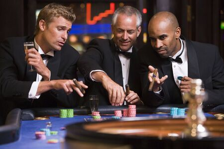 gambling parlour: Three men in casino playing roulette and smiling (selective focus)