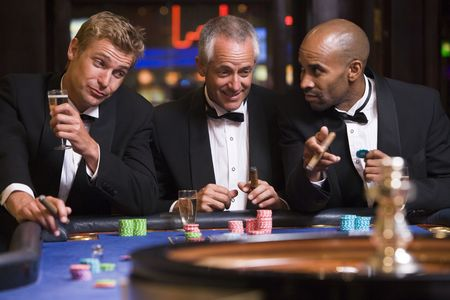 Three men in casino playing roulette and smiling (selective focus) Stock Photo - 3194459