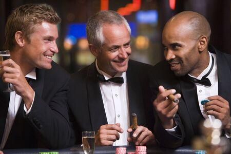 roulette table: Three men in casino playing roulette and smiling (selective focus)