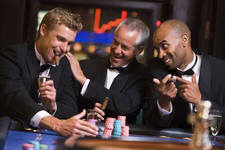 Three men in casino playing roulette and smiling (selective focus)