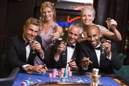 gamers: Five people in casino playing roulette and smiling (selective focus)