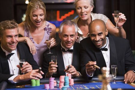 gambling parlour: Five people in casino playing roulette and smiling (selective focus)