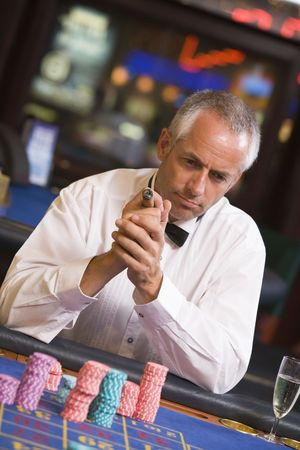 Man in casino playing roulette and smoking cigar (selective focus) Stock Photo - 3194513