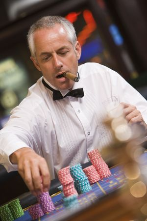 gambling parlour: Man in casino playing roulette and smoking cigar (selective focus)