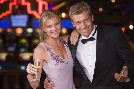gambling parlors: Couple in casino with cigar and champagne smiling (selective focus)