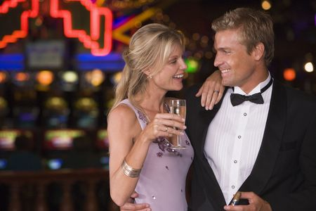 caucasoid race: Couple in casino with cigar and champagne smiling (selective focus)