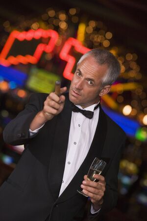 one armed: Man in casino with cigar and champagne pointing (selective focus)