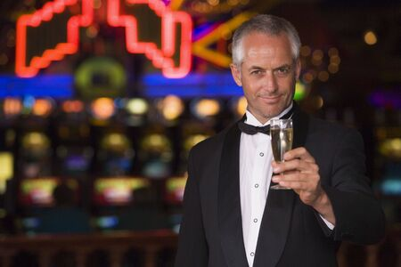 parlours: Man in casino with champagne smiling (selective focus)