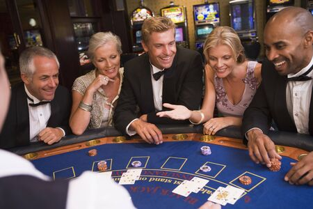 Five people in casino playing blackjack and smiling (selective focus)