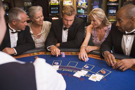 gambling parlour: Five people in casino playing blackjack and smiling (selective focus)