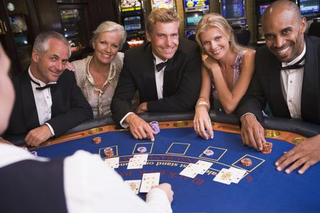 gamers: Five people in casino playing blackjack and smiling (selective focus)