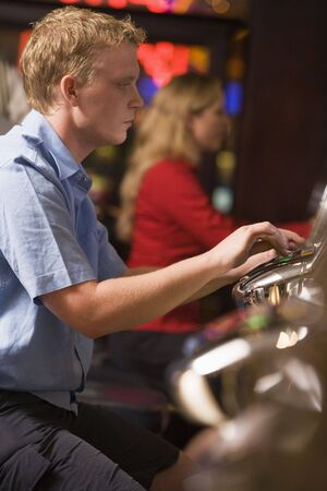 caucasoid race: Man in casino playing slot machine with people in background (selective focus) Stock Photo