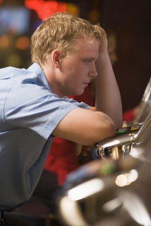 slots: El hombre en el casino de juego tragamonedas frustrado con la gente en el fondo (enfoque selectivo)