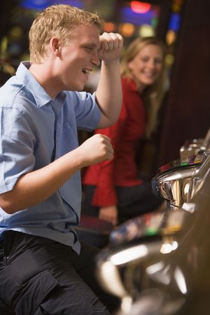 gambling parlour: Man in casino playing slot machine smiling with people in background (selective focus)