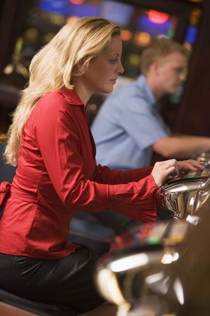 parlours: Woman in casino playing slot machine with people in background (selective focus) Stock Photo