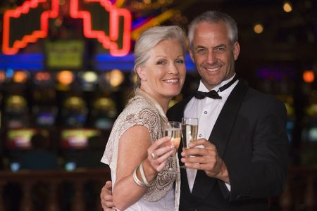 gambling parlour: Couple in casino with champagne smiling (selective focus) Stock Photo
