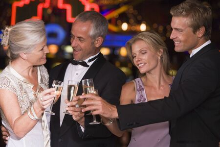 saluting: Two couples in casino toasting champagne smiling (selective focus) Stock Photo