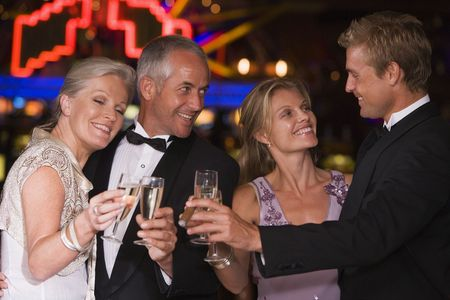 Two couples in casino toasting champagne smiling (selective focus) photo