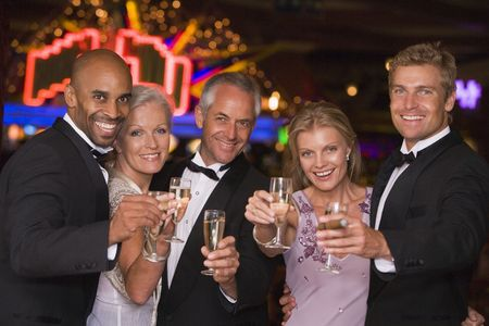 Five people in casino with champagne smiling (selective focus)