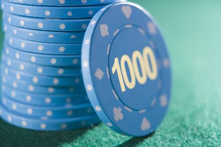 gambling parlors: Poker chips piled on a poker table with one thousand chip showing (close upselective focus) Stock Photo