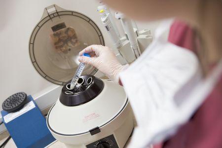 Embryologist putting sample into centrifuge (selective focus) photo