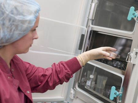 Embryologist putting sample into incubator (selective focus) photo